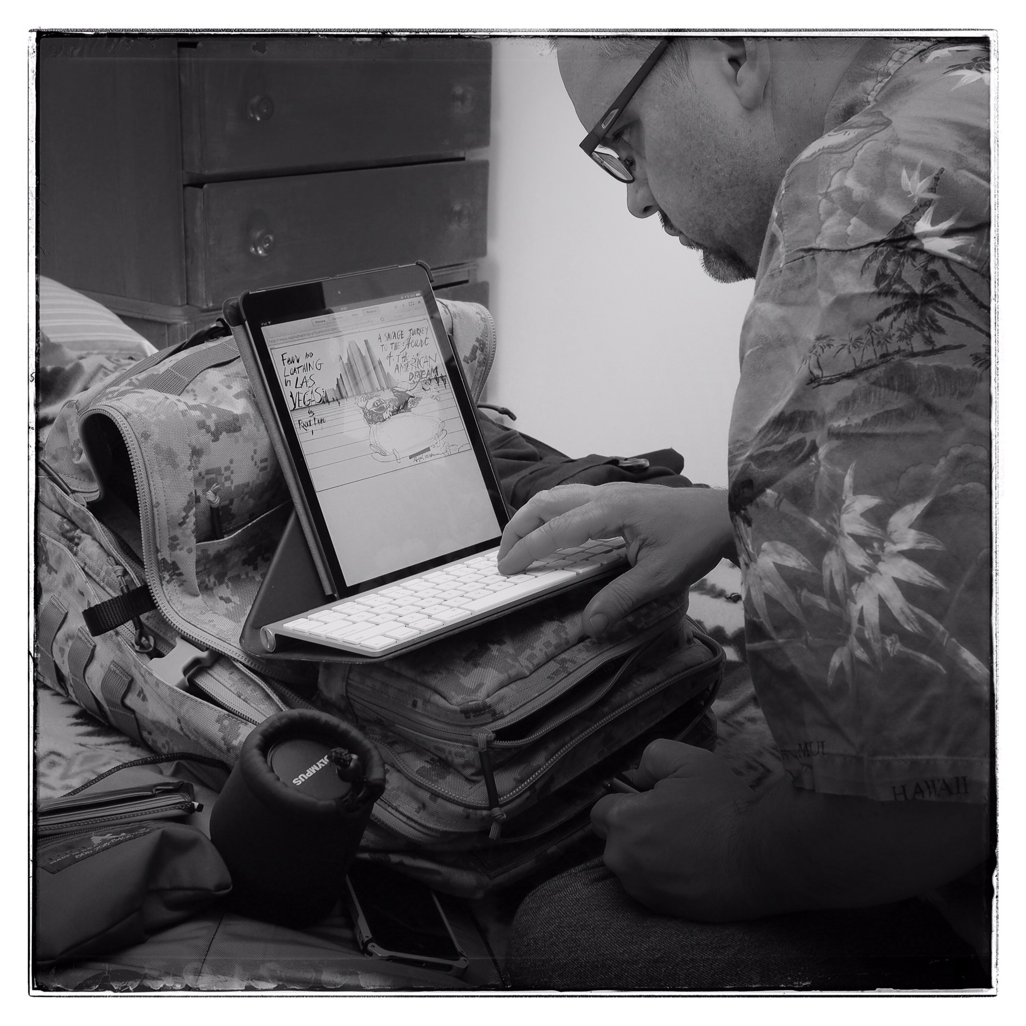 Author using iPad resting on backpack