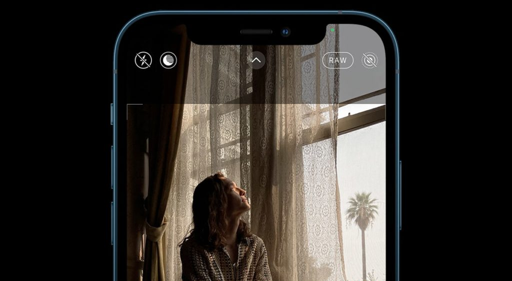 iPhone with camera app open taking photo of woman sitting in a window